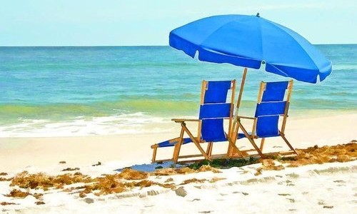 Two Blue Chairs and Umbrella on Beach